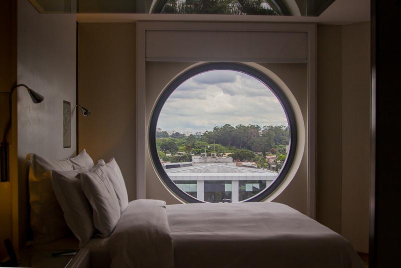Le Fashionaire Hotel Unique quarto cama almofadas janela redonda hotel unique sao paulo 5880 PT 805x537
