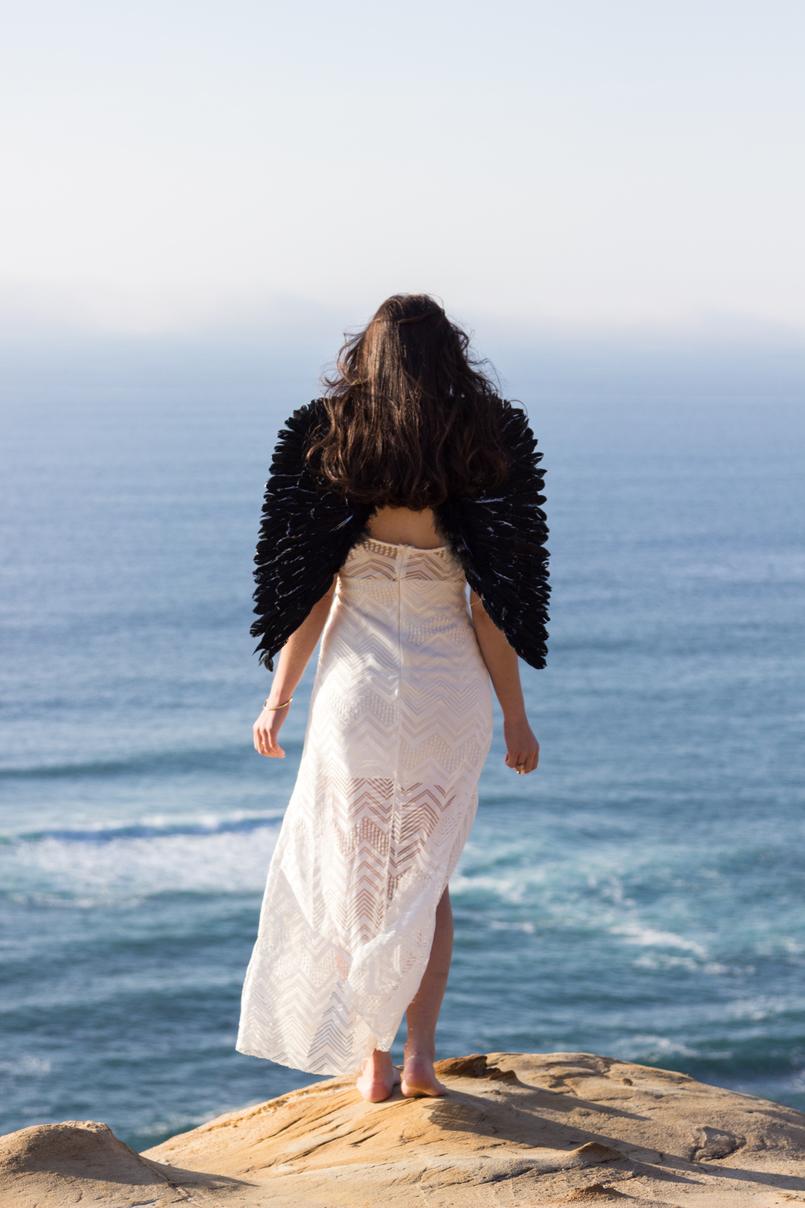 Le Fashionaire O lado obscuro que vive em nós blogueira catarine martins moda inspiracao vestido branco comprido renda asas anjo pretas praia mar sol penhasco ceu azul 2512 PT 805x1208