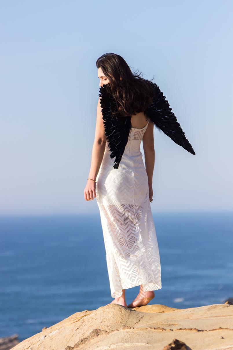 Le Fashionaire O lado obscuro que vive em nós blogueira catarine martins moda inspiracao vestido branco comprido renda asas anjo pretas praia mar sol penhasco ceu azul 2532 PT 805x1208