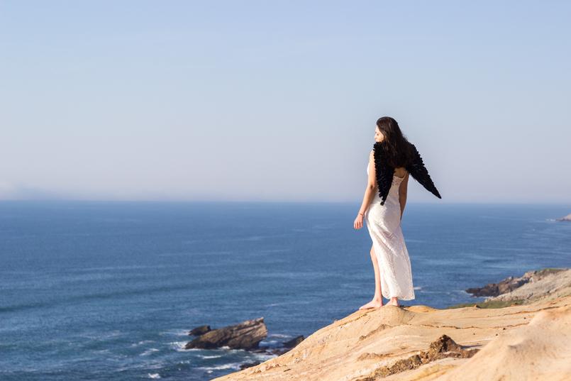 Le Fashionaire O lado obscuro que vive em nós blogueira catarine martins moda inspiracao vestido branco comprido renda asas anjo pretas praia mar sol penhasco ceu azul 2543 PT 805x537
