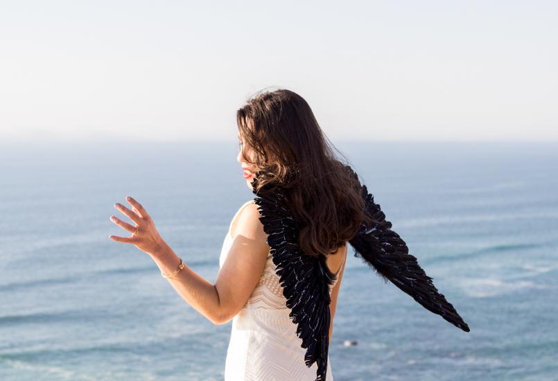 Le Fashionaire O lado obscuro que vive em nós blogueira catarine martins moda inspiracao vestido branco comprido renda asas anjo pretas praia mar sol penhasco ceu azul 2554 PT 805x550