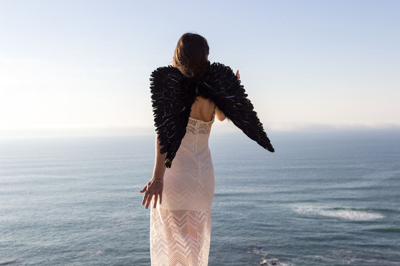 Le Fashionaire O lado obscuro que vive em nós blogueira catarine martins moda inspiracao vestido branco comprido renda asas anjo pretas praia mar sol penhasco ceu azul 2594 PT 805x537