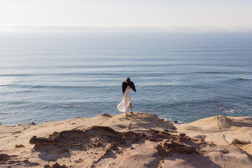 Le Fashionaire O lado obscuro que vive em nós blogueira catarine martins moda inspiracao vestido branco comprido renda asas anjo pretas praia mar sol penhasco ceu azul 2627 PT 805x537