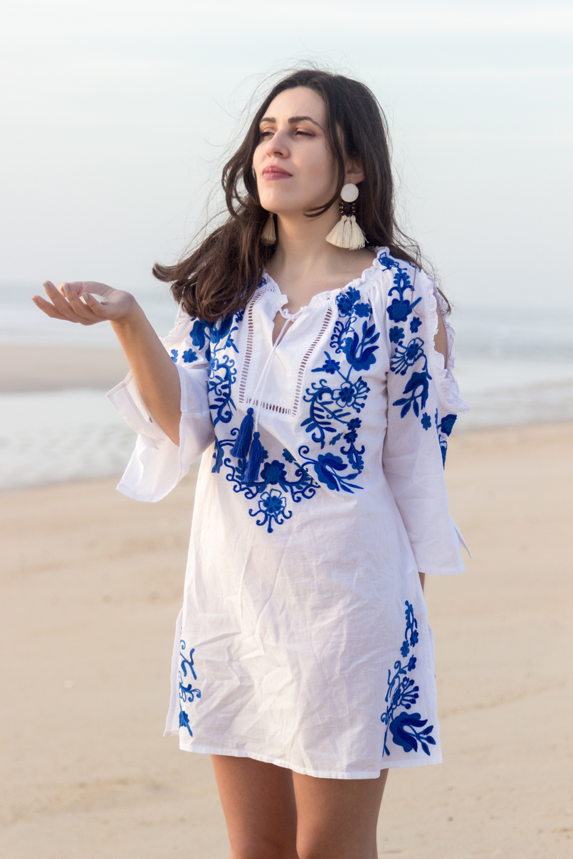 Le Fashionaire Buying clothes at Primark: yay or nay? blogger catarine martins white embroidered blue cotton primark dress white bold tassels brown earrings beach sand sea 3056 EN 805x1208