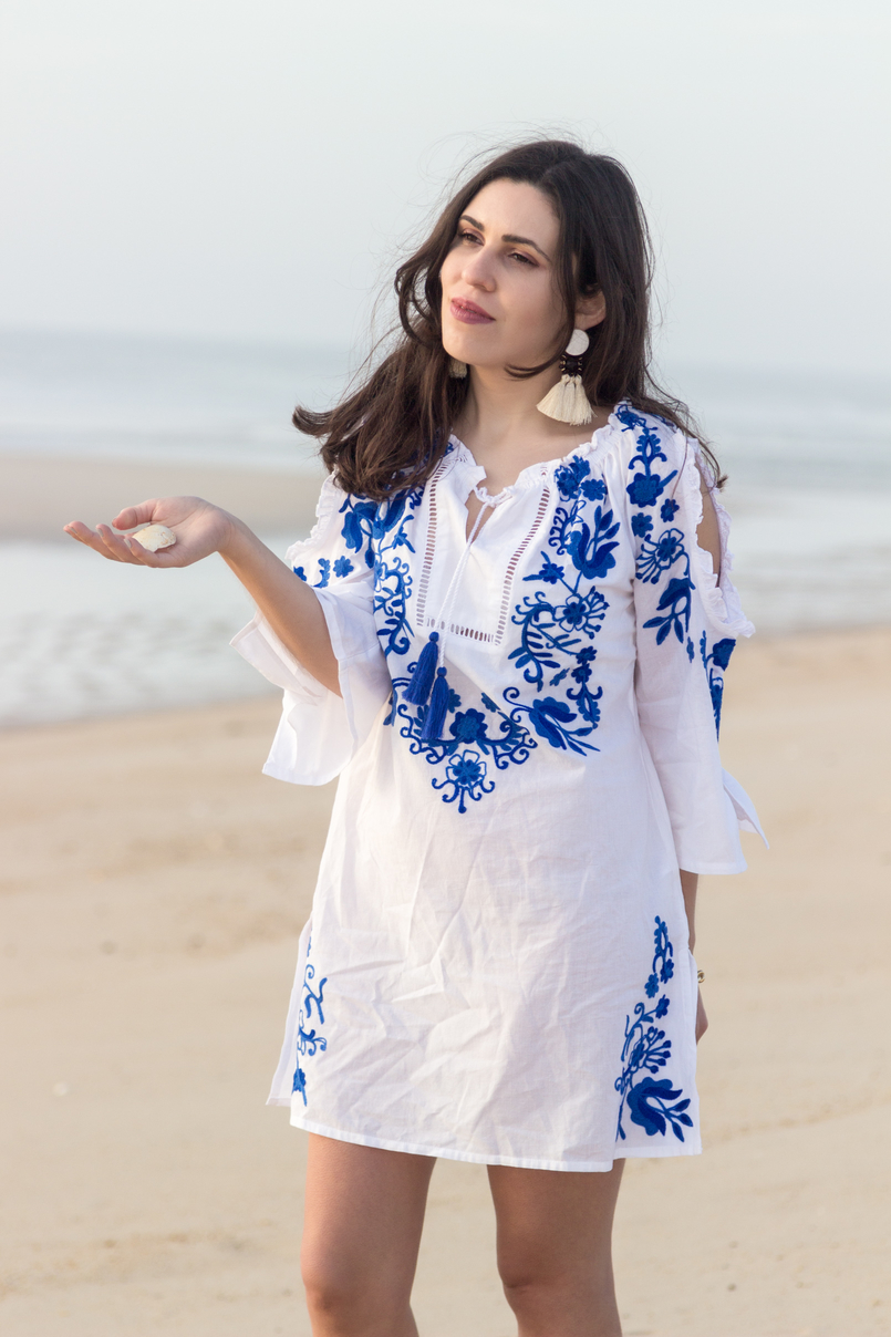 Le Fashionaire Buying clothes at Primark: yay or nay? blogger catarine martins white embroidered blue cotton primark dress white bold tassels brown earrings beach sand sea 3058 EN 805x1208