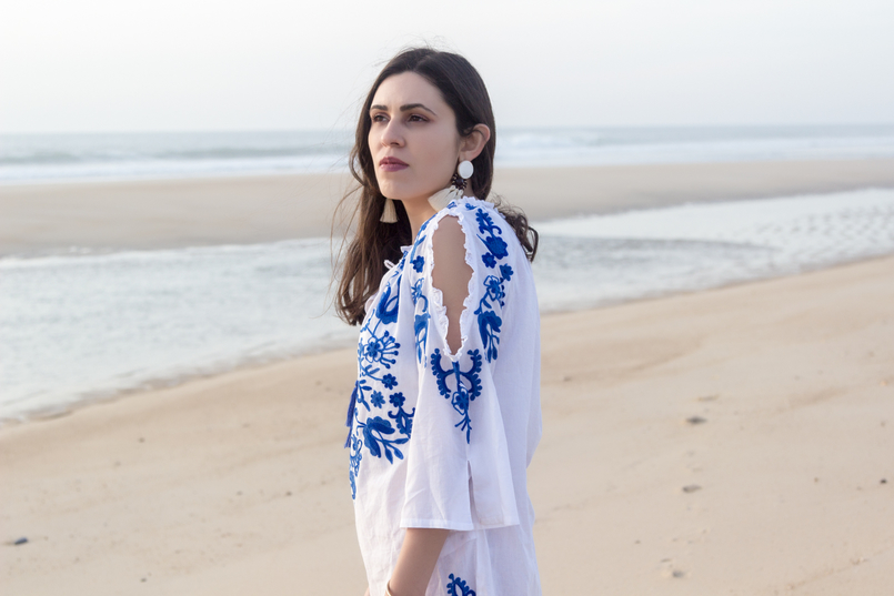 Le Fashionaire Buying clothes at Primark: yay or nay? blogger catarine martins white embroidered blue cotton primark dress white bold tassels brown earrings beach sand sea 3080 EN 805x537
