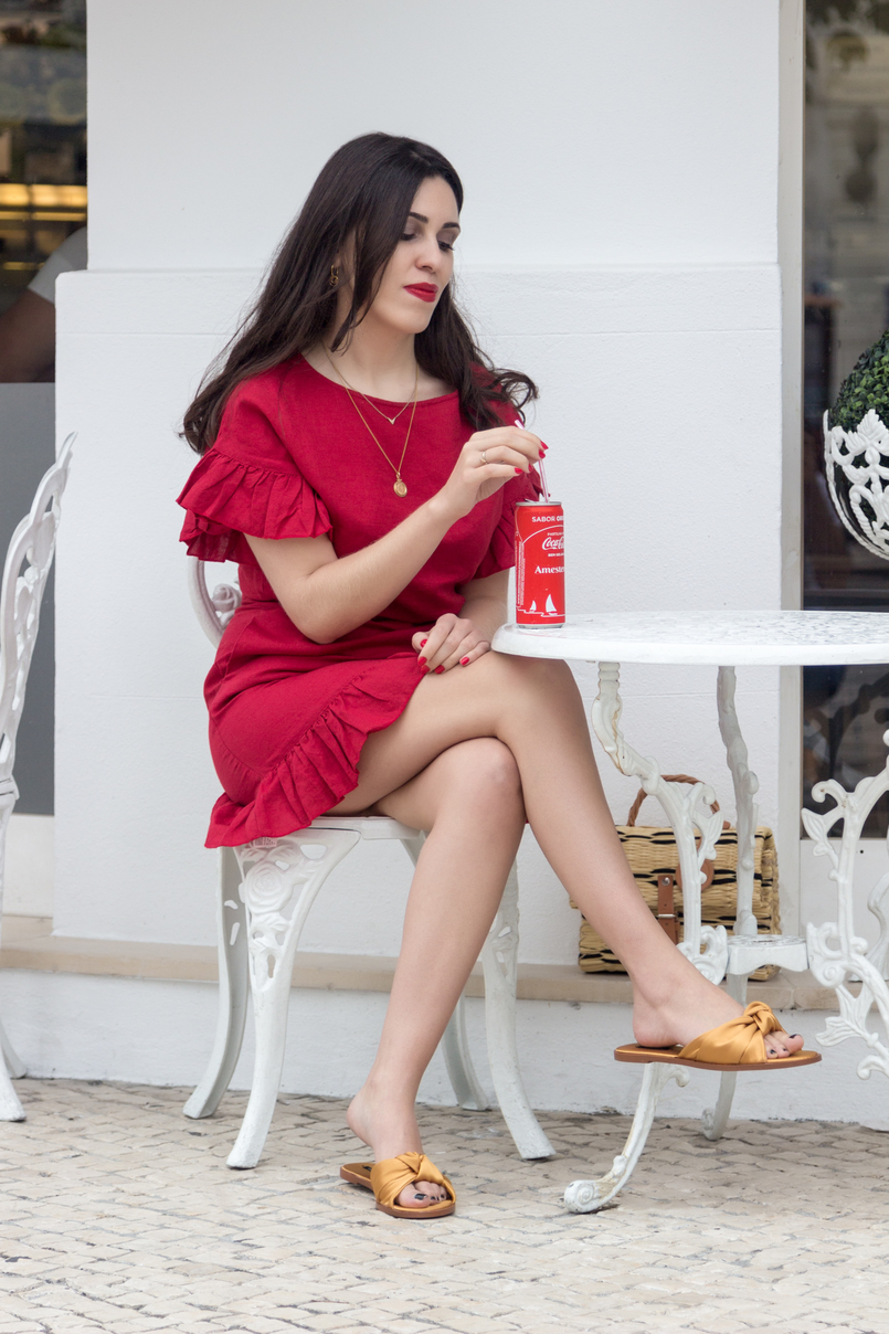Le Fashionaire Why is everybody wearing this red dress? linen red mango ruffles dress mango golden necklaces dark yellow bow satin zara slides coke red white chairs table coffee shop 4460 EN 805x1208