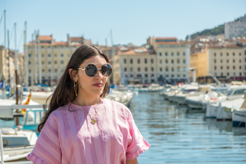 Le Fashionaire Why traveling is so important? marseille landscape boats sea sky blue linen stripes pink zara blouse round gold sunglasses 1350 EN 805x537