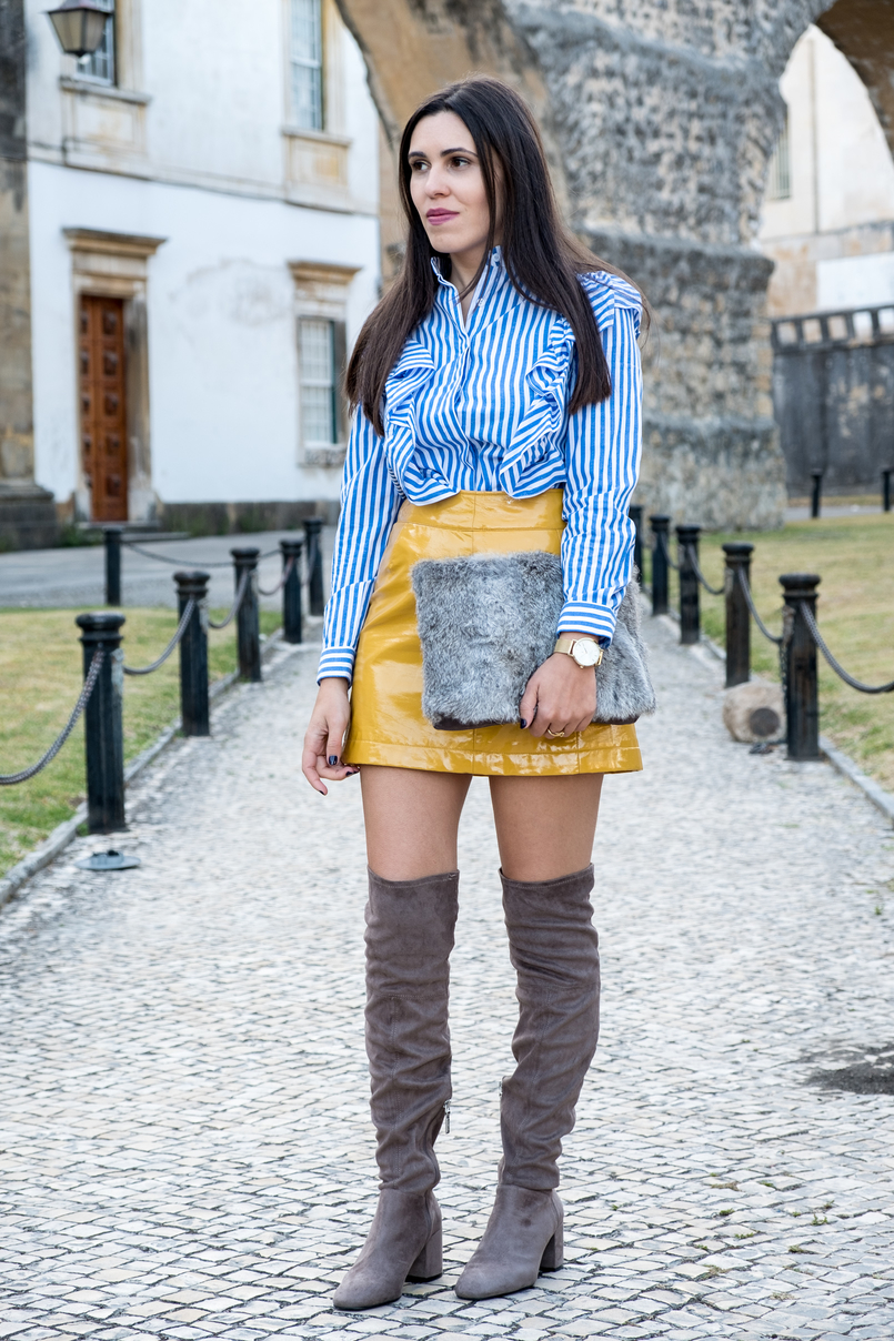 Le Fashionaire On trend: Vinyl white blue vertical stripes ruffles shein shirt yellow vinyl sfera skirt over knee suede grey over knee bershka boots faux fur grey sfera clutch 4173 EN 805x1208